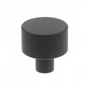 industriell knopp svart metall, rund med räfflat mönster.