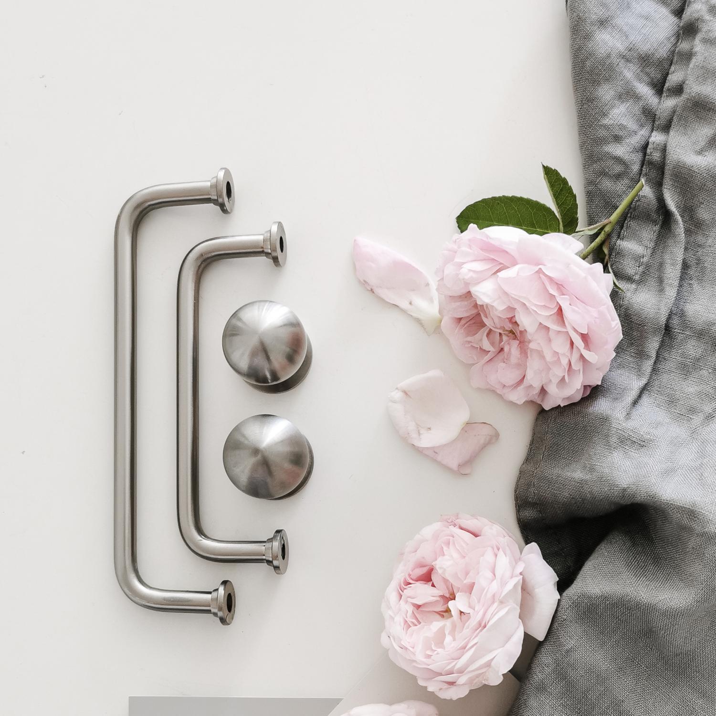 Rostfria köksbeslag med rosa pioner och grå kökshandtag
