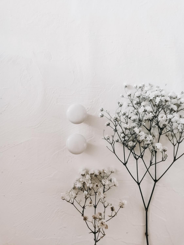 Två vita porslinsknoppar och ett knippe brudslöja