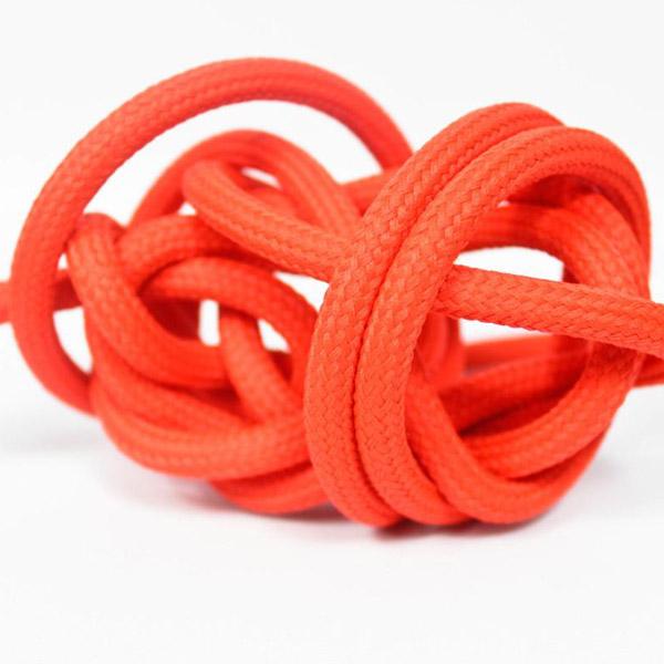 Körsbärsröd textilkabel. Kabeln är ojordad och finns i flera olika längder.