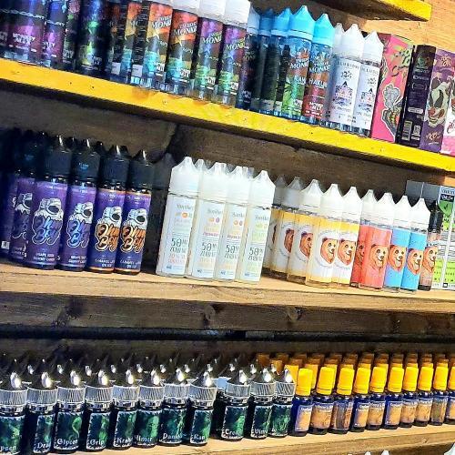 butikshyllor av trä med långa rader av e-juice uppställda för dispay