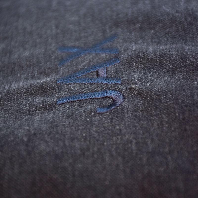 Närbild på mörkgrå bäddyna till katt eller hund med namnet Jax graverat i blått.