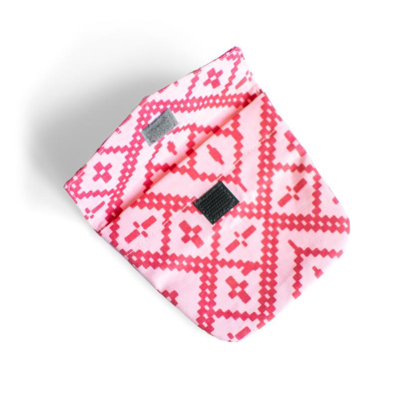 Liten rosa och rödmönstrad koppelväska med kardborre knäppning.