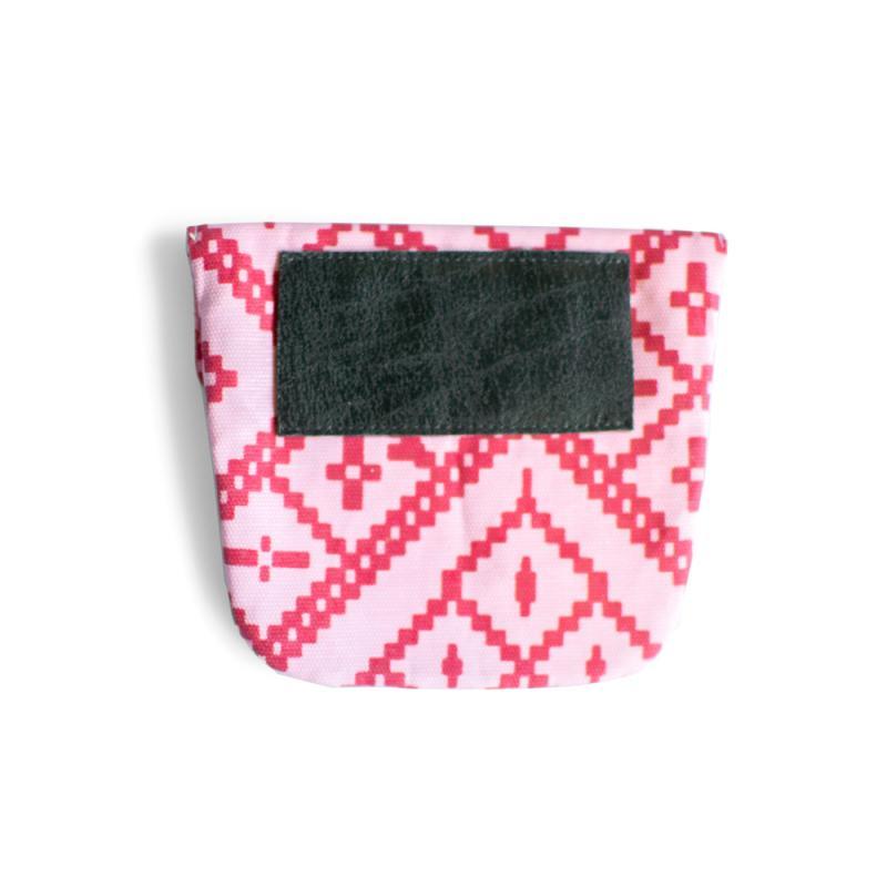 Liten rosa och rödmönstrad koppelväska med läderfäste.