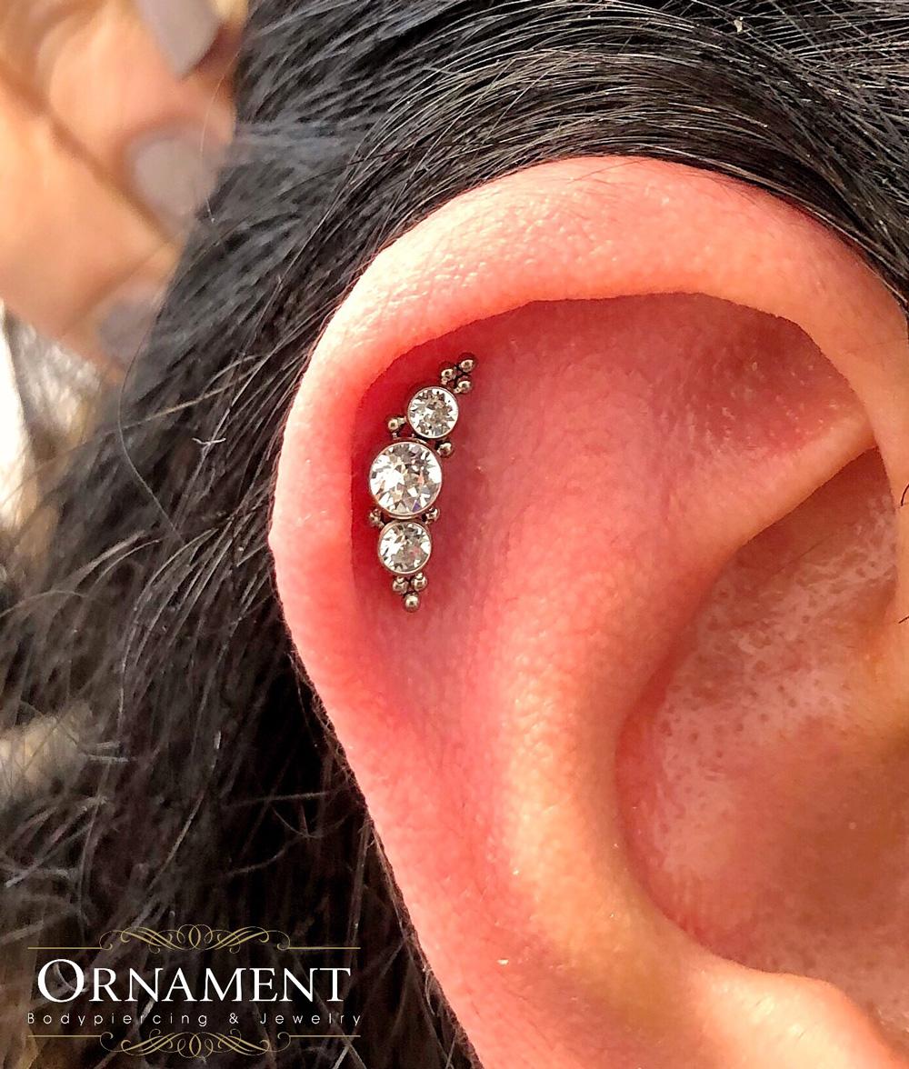 Öra med helixpiercing och smycke i silvrigt nickelfritt stål med tre kristaller.