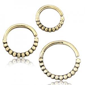 Liten tunn ring i guldig mässing med små kulor som dekoration. Passar till piercingar.