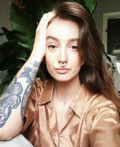 Brungårgig tjej med tatuering på armen och en septumpiercing i guld.