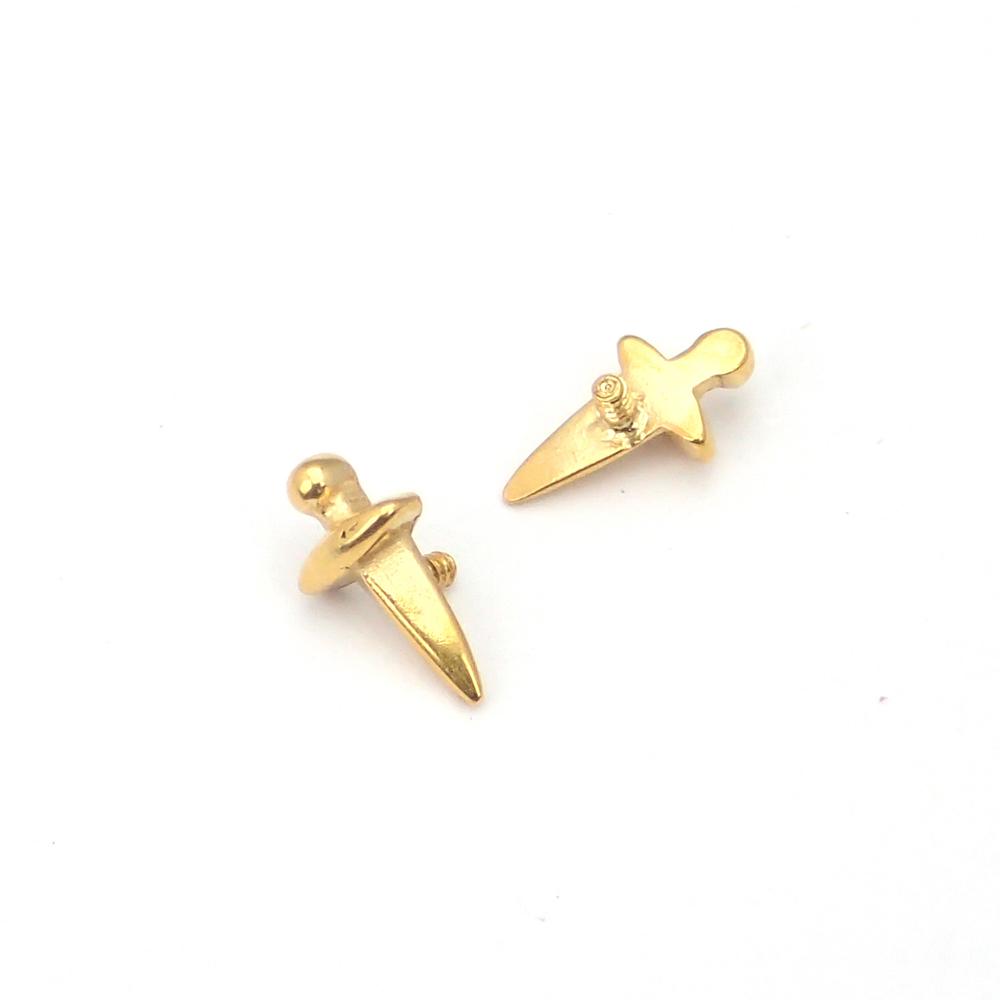 Ett piercingsmycke i guldpläterat kirurgiskt stål med motiv av en liten dolk.