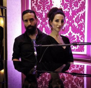 Två musiker, Madeleine och Richard från bandet Eleine står vid ett piano och en rosa bakgrundsvägg