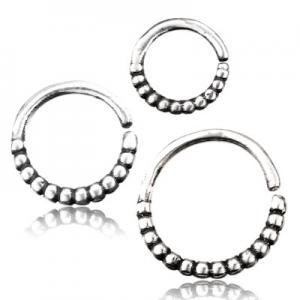 Silvrig ring till piercing med små detaljer. Smycket används till öron, septum eller daith.