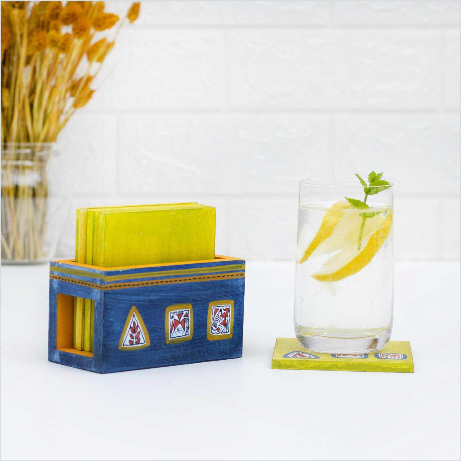 Wooden coaster set placed in a holder in blue and yellow colors standing on a white table next to a glass of water with lemon and mint leaves on top of a coaster with a white wall and dried flowers in the background