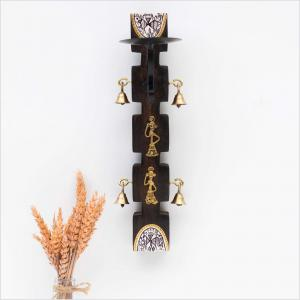 Dark brown candle stand with brass bells and tribal motifs hanging on a white wall next to dried oat leaves kept in a vase
