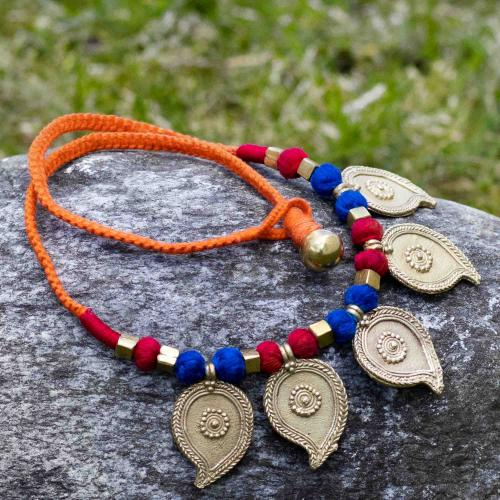 Brass bead necklace with leaves on an orange string coupled with blue and red silk bead