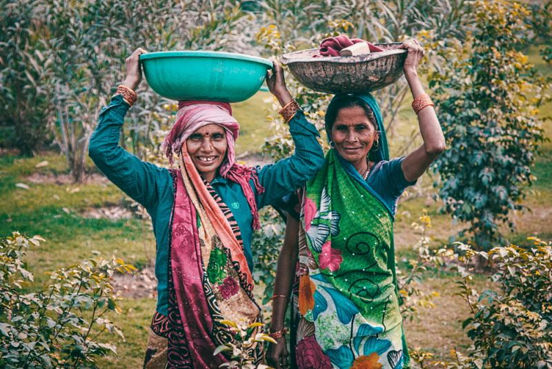 Two women in saris standing in nature, each holding a dish on their head
