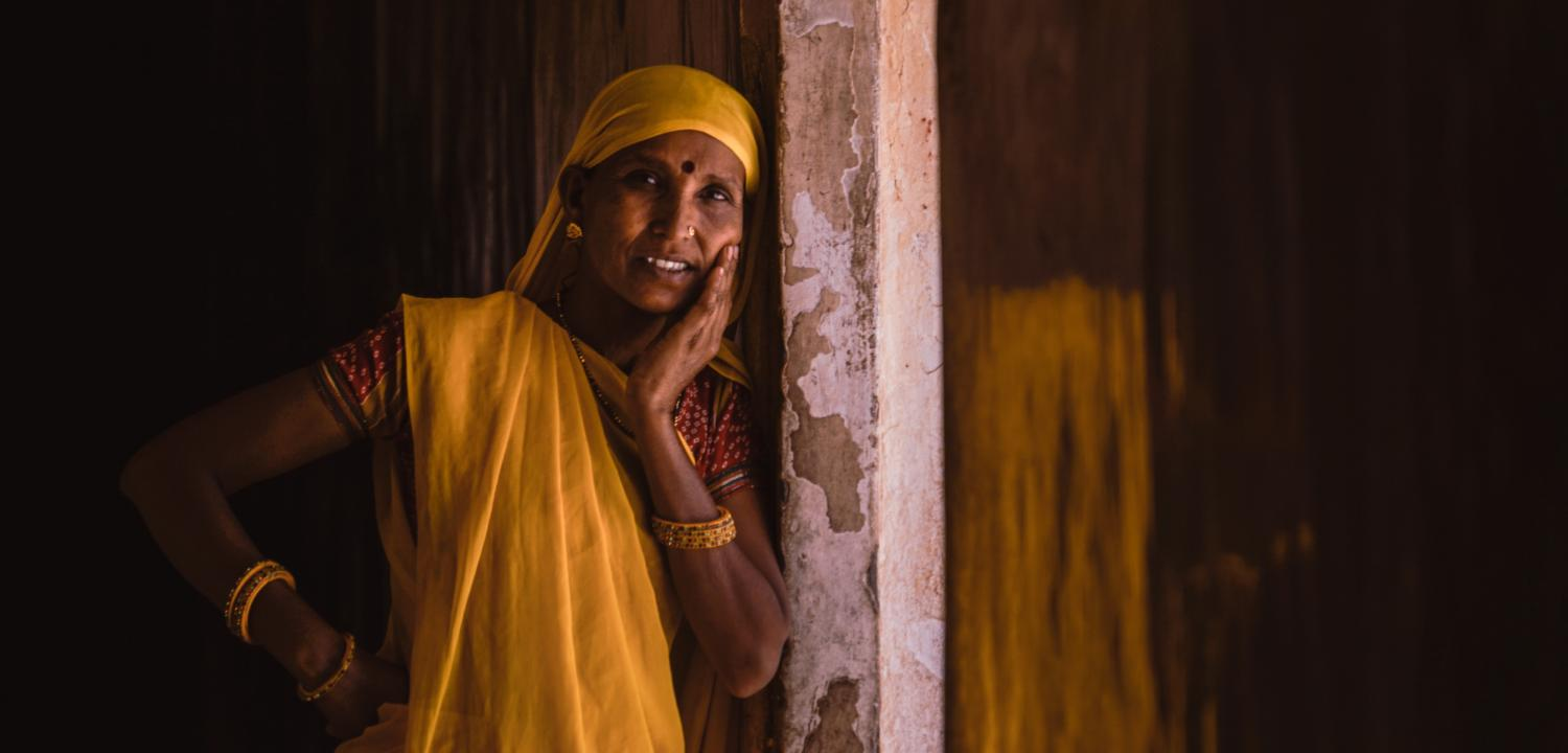 Portrait of a woman in yellow sari leaning against a pillar with her head resting on her left hand