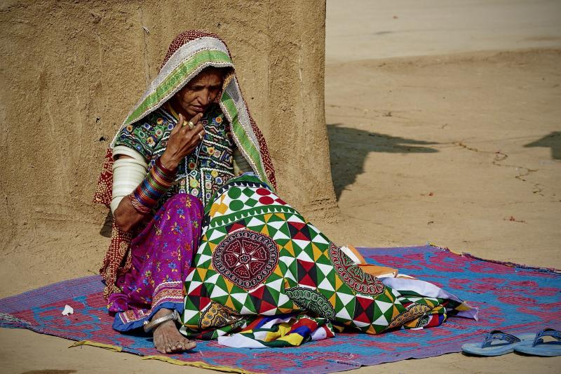 A woman in a sari sitting on a purple blanket outside, crafting a colorful embroidered fabric by hand