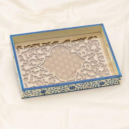 Beige wooden tray with blue flower motifs placed on a white cloth