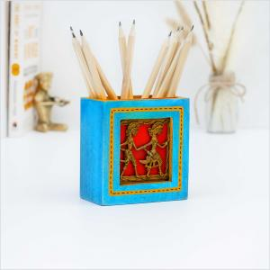 Blue pen stand with brass figurines holding pens placed on a white surface with a brass figurine, dried flowers and books in the background