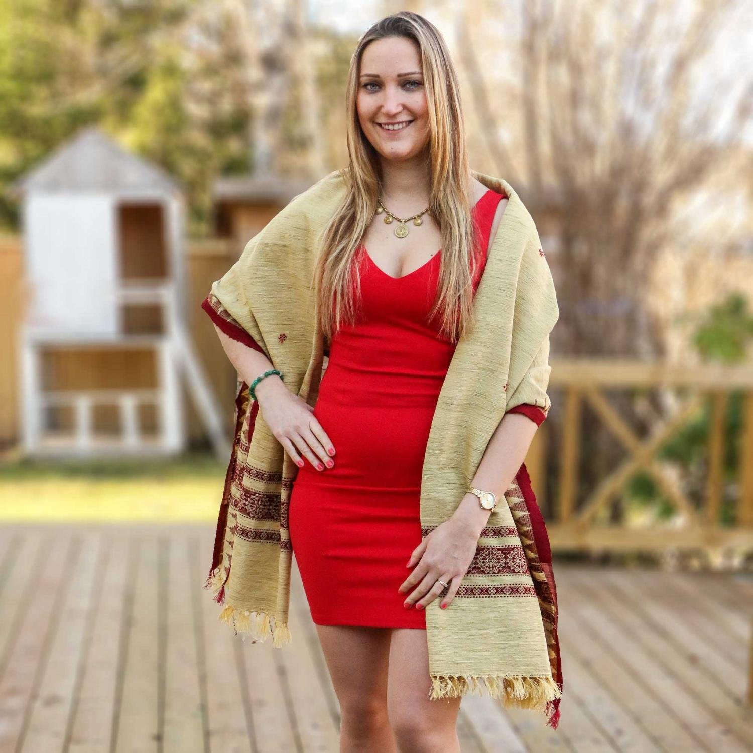 Woman in red dress wearing a golden shawl with red pattern edge and brass necklace posing on a wooden deck