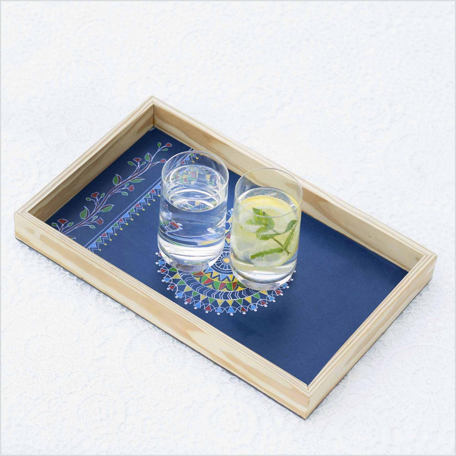 Blue color Mandala design tray with the sun shaped in the center of tray kept on a white surface with the glass of water and lemonade kept on a tray