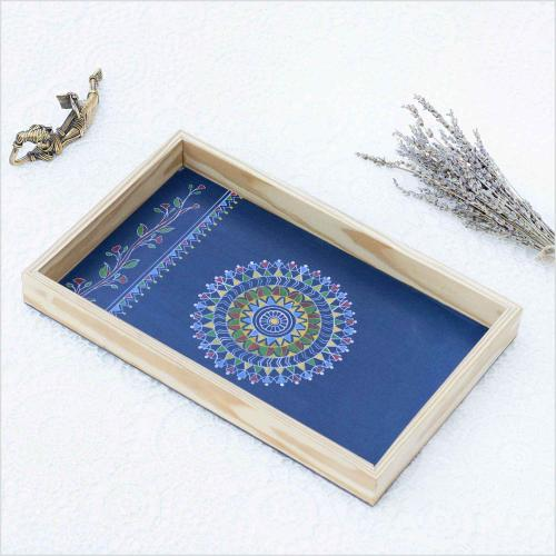 Blue color Mandala design tray with the sun shaped in the center of tray kept on a white surface  with the brass figurine and dried levendar kept beside it.