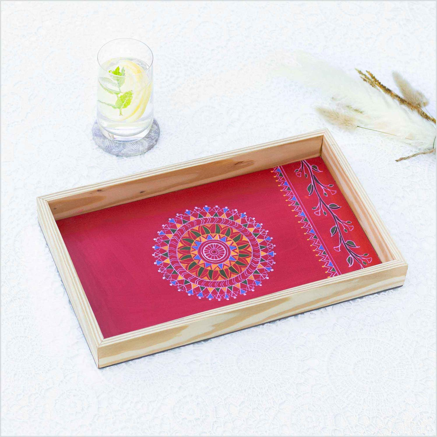Red color Mandala design tray with the sun shaped in the center of tray kept on a white surface with the glass of  lemonade and leaves kept behind it and dried oats leaves in the right