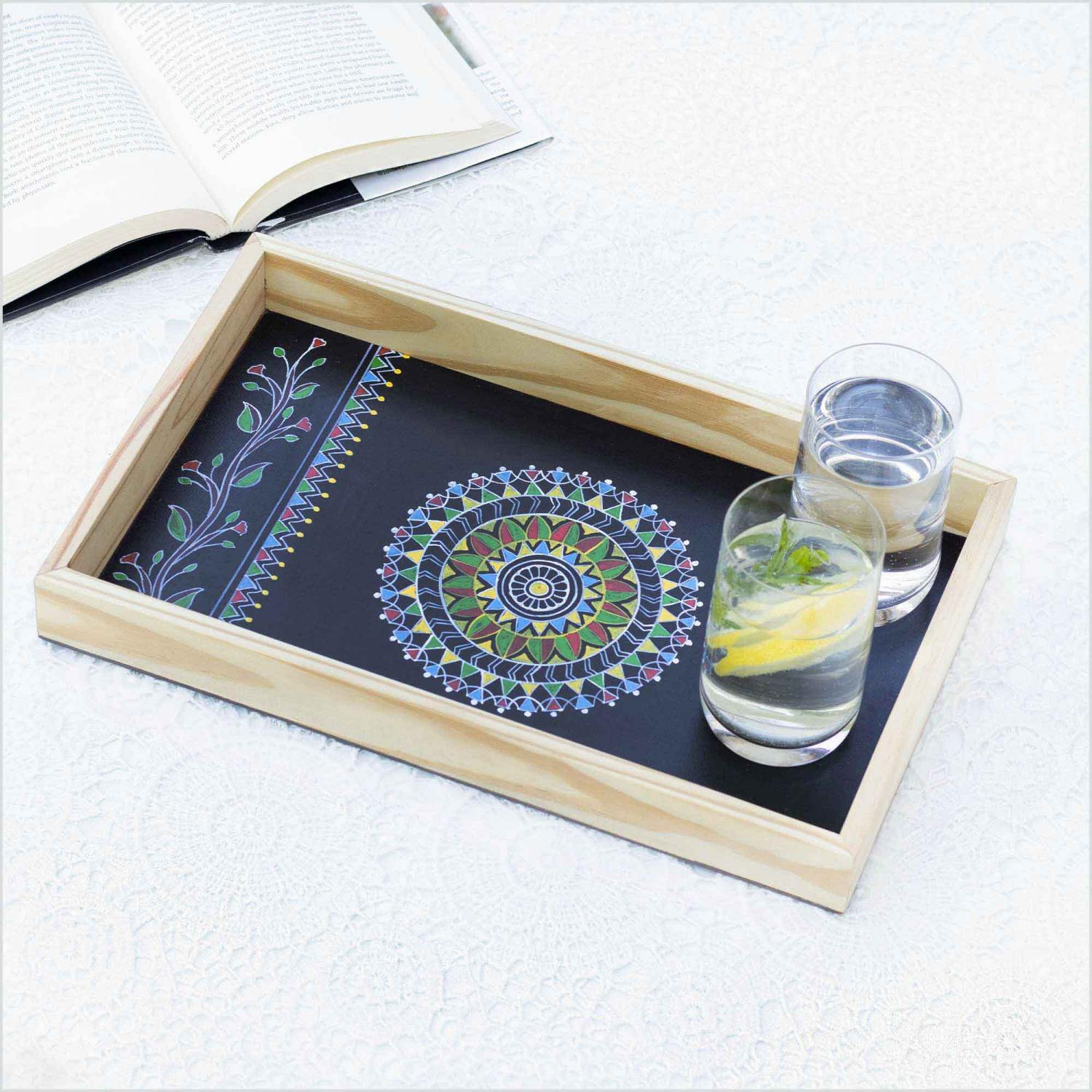 Black color Mandala design tray with the sun shaped in the center of tray kept on a white surface with the glass of water and lemonade in a tray and book kept beside it.