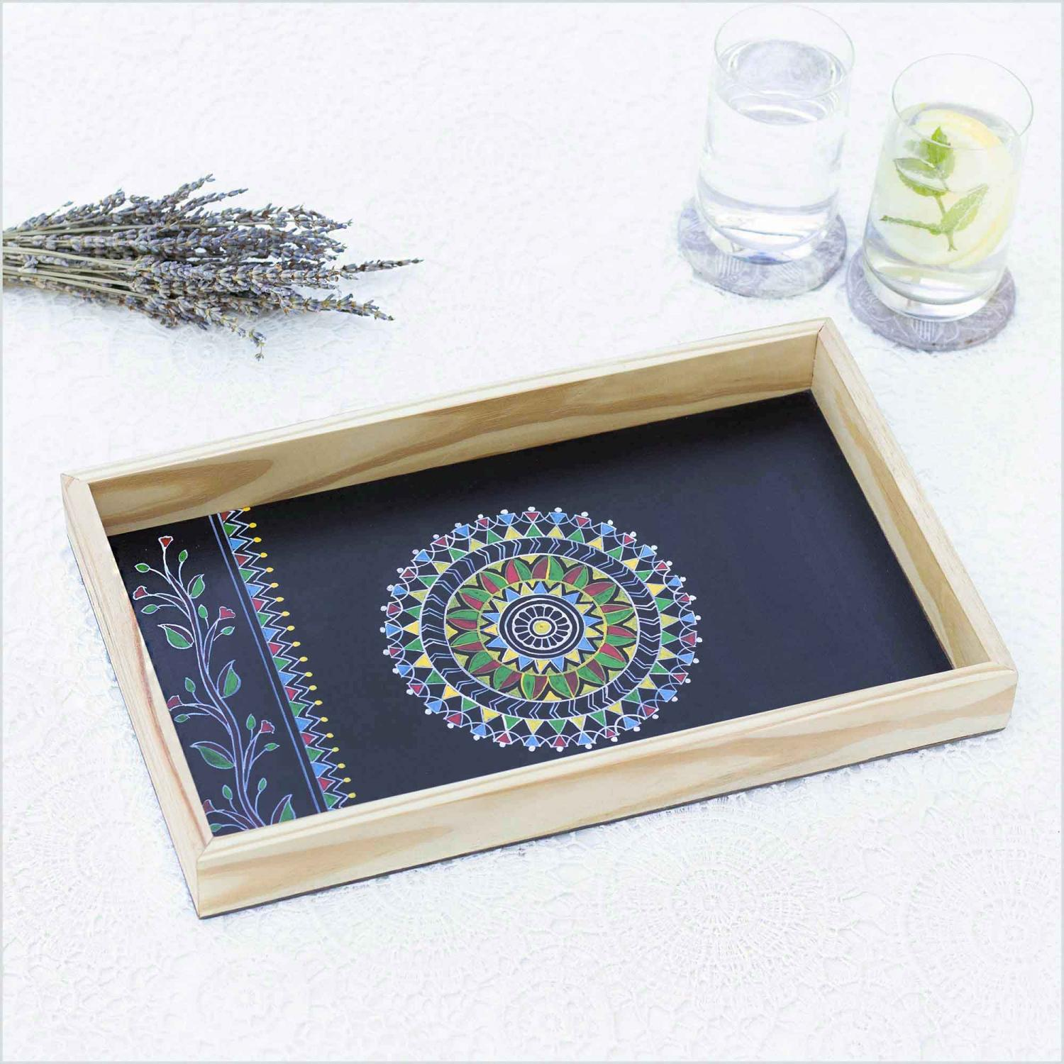 Black color Mandala design tray with the sun shaped in the center of tray kept on a white surface with the glass of water and lemonade in right and dried lavender in left