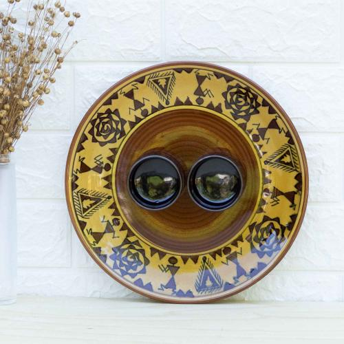 Ceramic platter with two attached bowls with the combination of mustard yellow, brown and black colors, standing against a white wall next to a vase filled with dried flowers