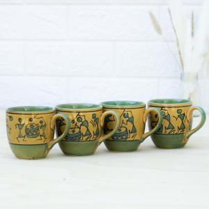 Four coffee mugs in green and yellow colors with paintings of tribal motifs, placed in a row on a table with a vase filled with dried flowers and a white wall in the background