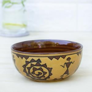 Ceramic bowl with a mix of mustard yellow and brown color decorated in tribal art, placed on a table with a glass of water in the background and a white wall