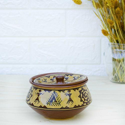 Ceramic bowl with lid in a combination of mustard yellow and brown color decorated with tribal art, placed on a white table with a vase filled with dried flowers and a white wall in the background