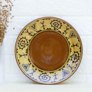 Ceramic dinner plate in brown color designed with intricate tribal art, standing against a white wall next to a vase filled with dried flowers