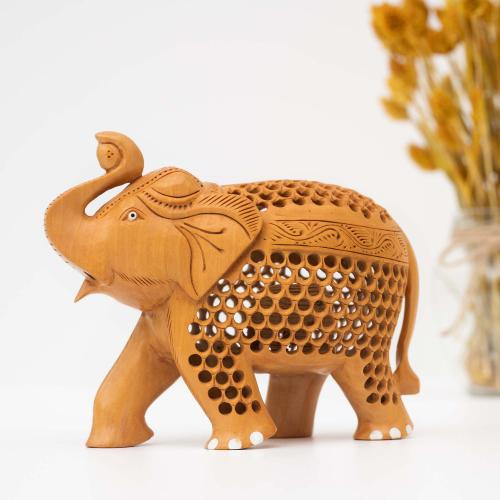 Wooden elephant figurine with mesh work placed on a white surface with a vase of dried flowers in the background.