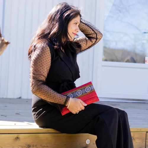 Dark haired woman in black clothes sitting outside on a wooden step holding a red clutch with decorative patterns with a white wall and a glass door in the background
