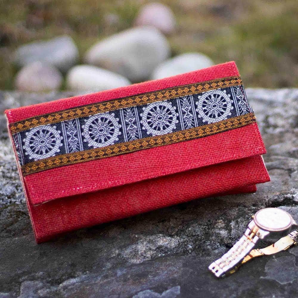 Jute clutch in red color with decorative patterns placed on a black rock with a watch beside it, with white stones and green grass in the background