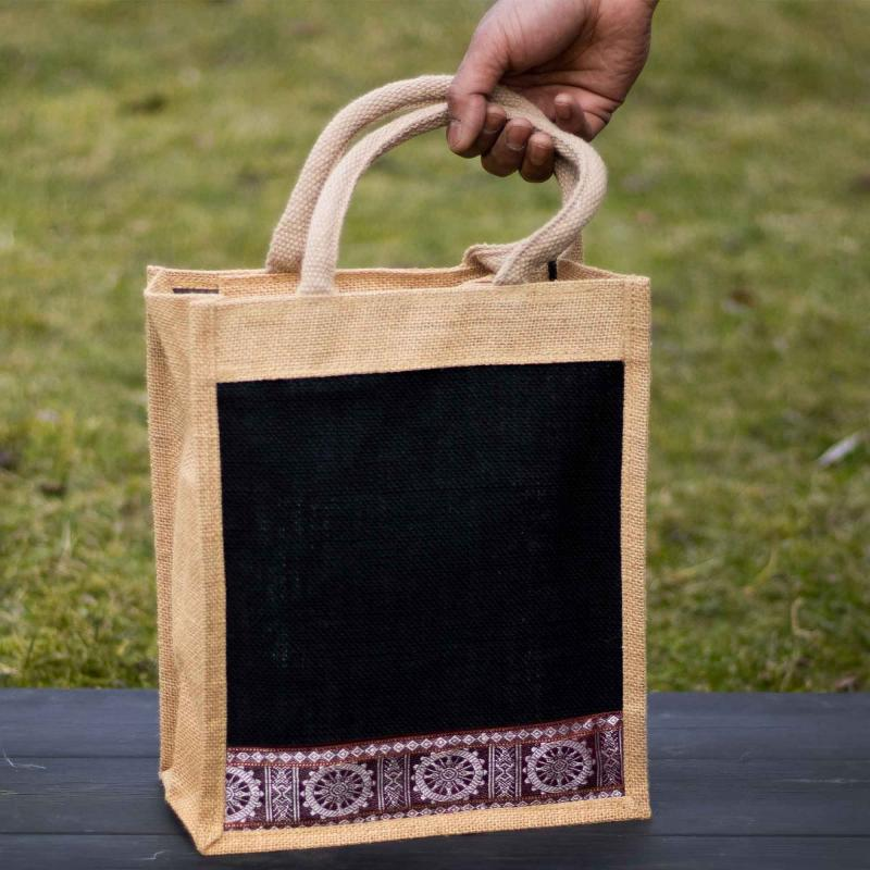 Jute bag in black and cream color with decorative patterns with a hand holding the handle, standing on black wood with green grass in the background