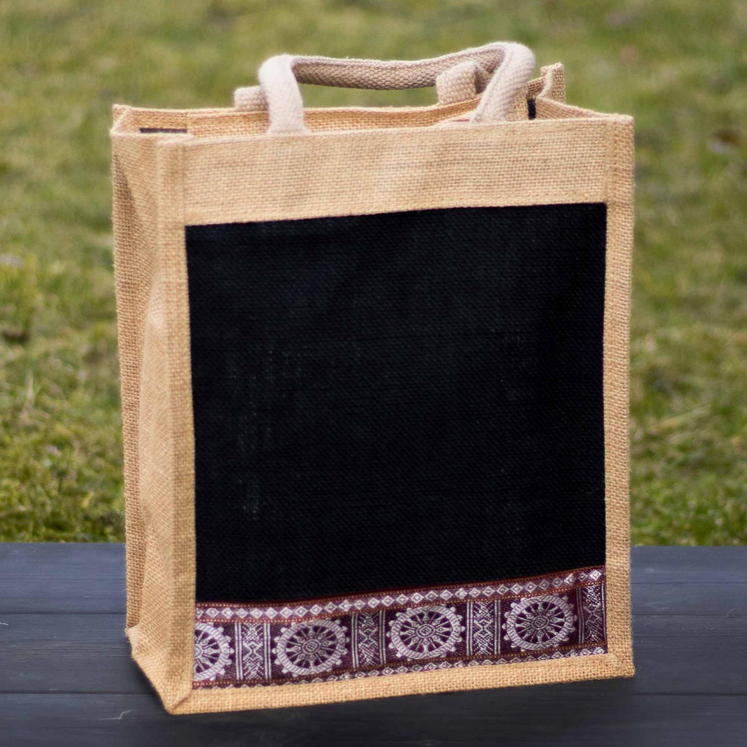 Jute bag in black and cream color with decorative patterns standing on black wood with green grass in the background