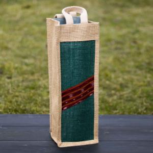 Jute wine bag in cream and patchwork in sea green color standing on black wood with green grass in the background