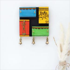Wooden key holder with blocks with a brass figurine and brass bells at the bottom with dried oat leaves vase