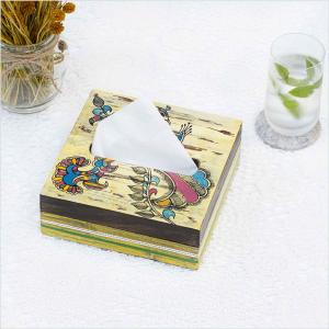 Wooden tissue box featuring a peacock design holding tissues placed on a white surface next to a glass of water with mint leaves and dried flowers