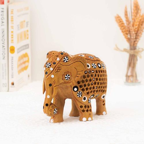 Wooden elephant figurine with black and white flower motifs placed on a white surface with a collection of books and a vase of oats in the background.