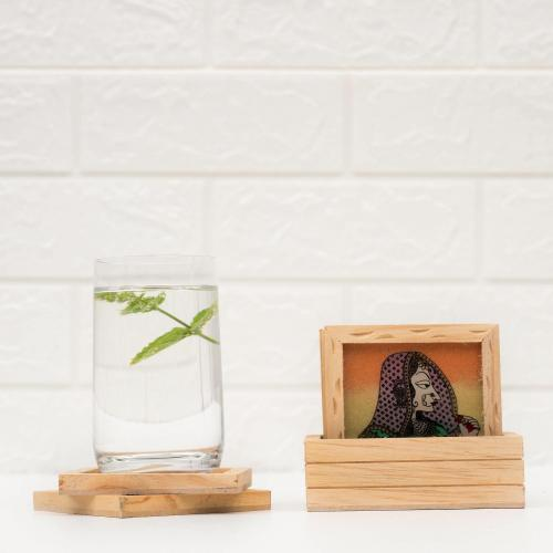 Wooden coaster set and holder with a queen motif placed on a white surface next to a glass of water with mint leaves placed on a coaster with a white wall in the background.