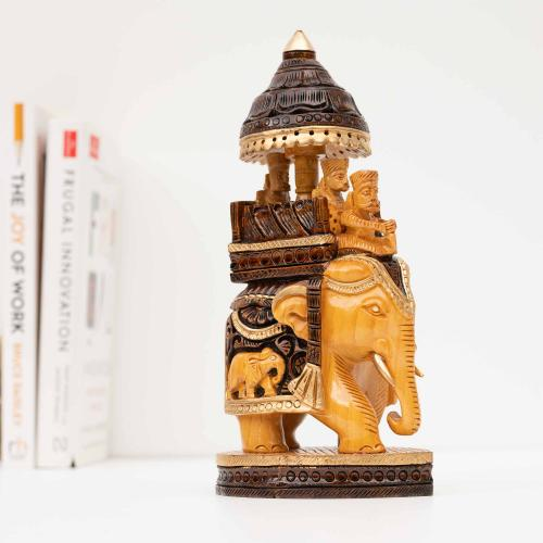 Wooden elephant sculpture with an umbrella on top in a mix of light wood and dark brown colors with gold accents placed on a white surface with a collection of books in the background.