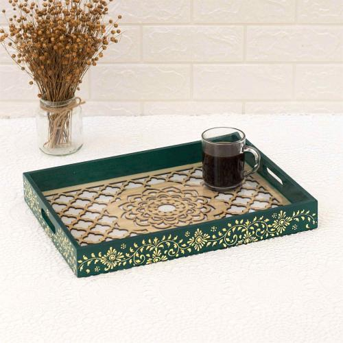 Wooden tray with fine golden acrylic motifs and carved flower decorations that hold a glass coffee cup and is placed on a white surface with a vase of dried flowers in the background