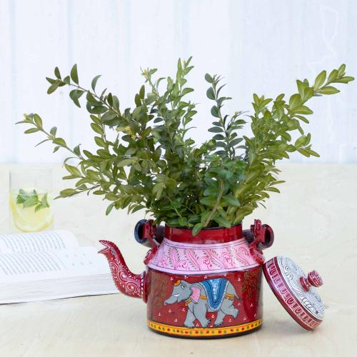 Red aluminium planter with an elephant filled with green twigs standing on a table with a book and a glass in the background