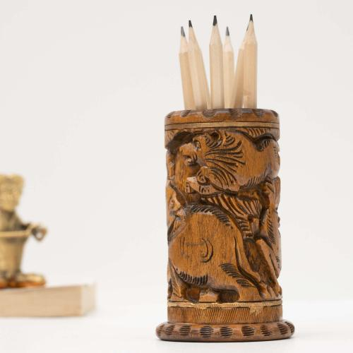 Wooden pen holder in dark brown color with detailed carvings holding pencils, placed on a white surface with a brass figurine in the background.