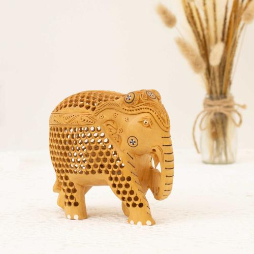 Wooden elephant figurine with mesh work placed on a white surface with a vase of dried pampas grass in the background.