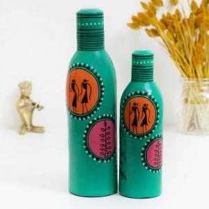 Decorative bottles painted in acrylic colors with emerald base, pink and orange with tribal motifs in black standing on a table with a brass musician and a vase with dried oats flower and a white background