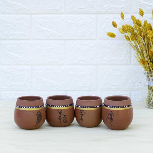 Four dark brown colored terracotta cups decorated with tribal art, standing on a table with a vase filled with dried flowers and a white wall in the background